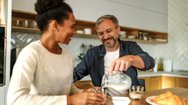 A couple sitting in the kitchen while eating a breakfast with whole grains.