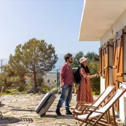A couple entering a rental home on a sunny day