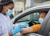 A healthcare professional giving a man COVID-19 vaccine while he sits in his car