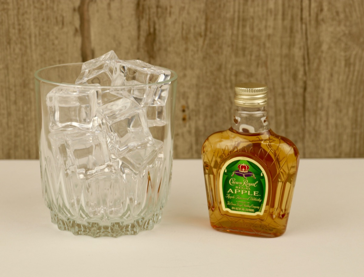 A full glass of ice next to a bottle of Crown Royal