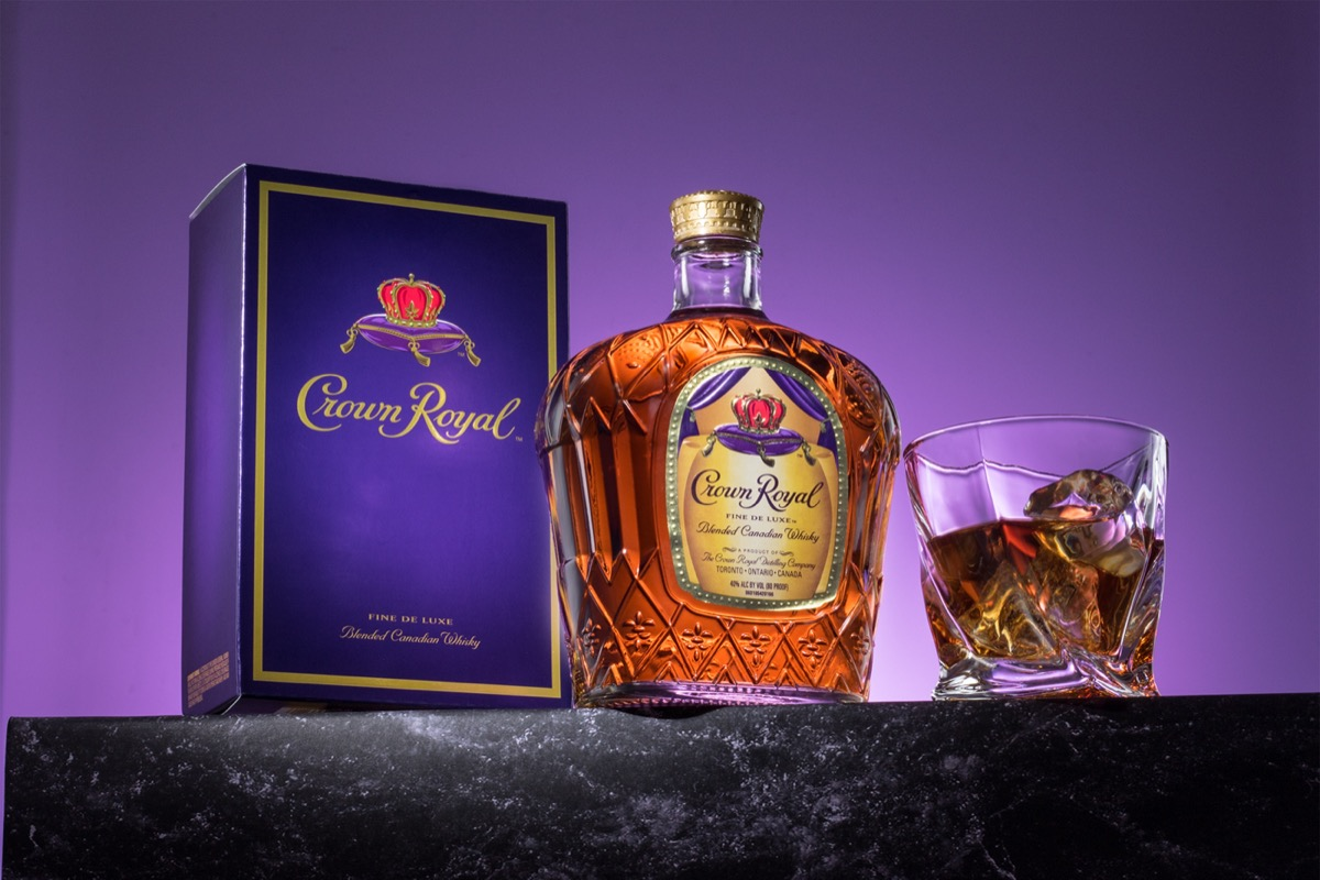 Bottle of Crown Royal, a glass, and a box in front of a purple background