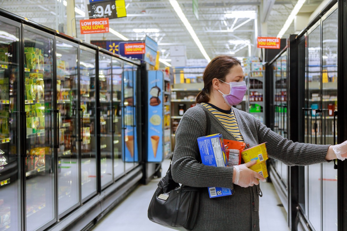 Walmart supermarket Los Angeles CA US 16 MAY 2020: Shopping on supermarket during the Coronavirus COVID-19 pandemic on customer in a supermarket choosing, with woman wearing disposable medical mask