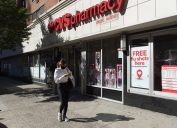 Manhattan, New York. October 08, 2020. A woman wearing a face mask walks in front of a CVS pharmacy Midtown with a sigh advertising free flu shots.