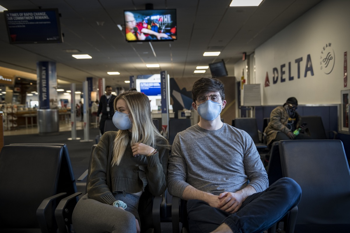 New York City, USA - March 21, 2020: A young man and woman wait at LaGuardia airport to board a flight to Orlando. On account of the ongoing coronavirus pandemic, they were among the many passengers wearing respirator masks for protection.