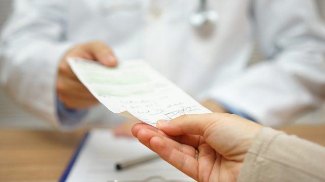 doctor handing prescription to patient