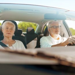 Older couple driving in car