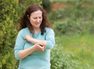 Woman scratching arm because it stings in a park with copy space