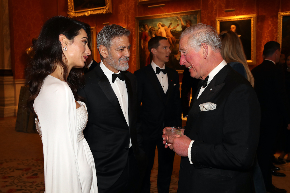 Amal Clooney and George Clooney speak to Prince Charles, Prince of Wales as they attend a dinner to celebrate The Prince's Trust, hosted by Prince Charles, Prince of Wales at Buckingham Palace on March 12, 2019 in London, England.