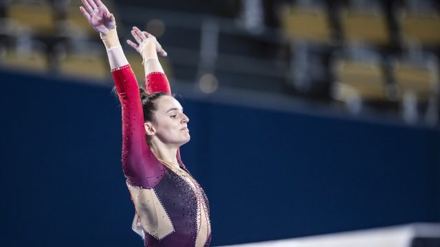 Olympic gymnast Pauline Schäfer in action on beam in a unitard.