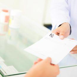 person handing prescription to pharmacist
