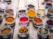 small glass bowls of spices on wooden table