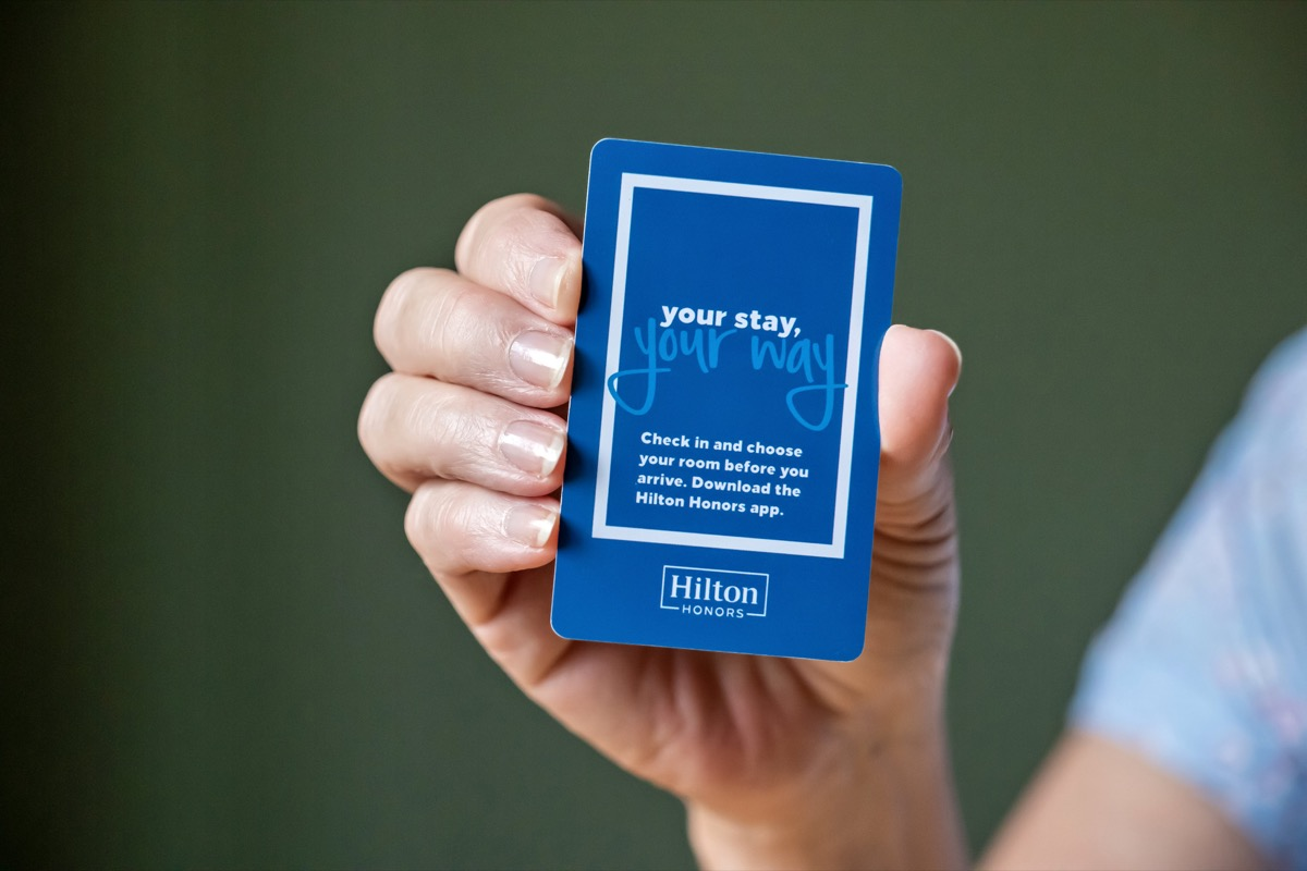 BEMIDJI, MN - 20 JUL 2020: Womans hand holding room security keycard for Hilton Hotels in close-up view. Advertising for Hilton Honors with the words your stay, your way written on front of card.