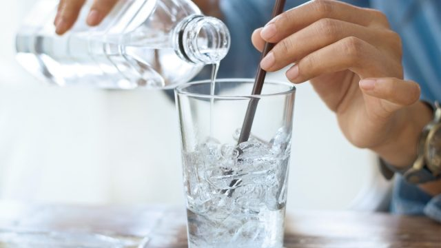 person pouring ice water into glass