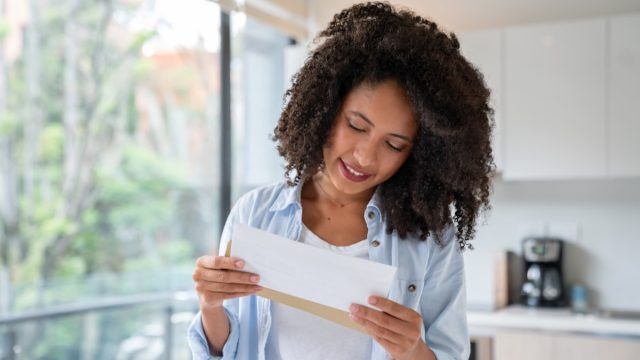 woman reading the mail at home and smiling - lifestyle concepts