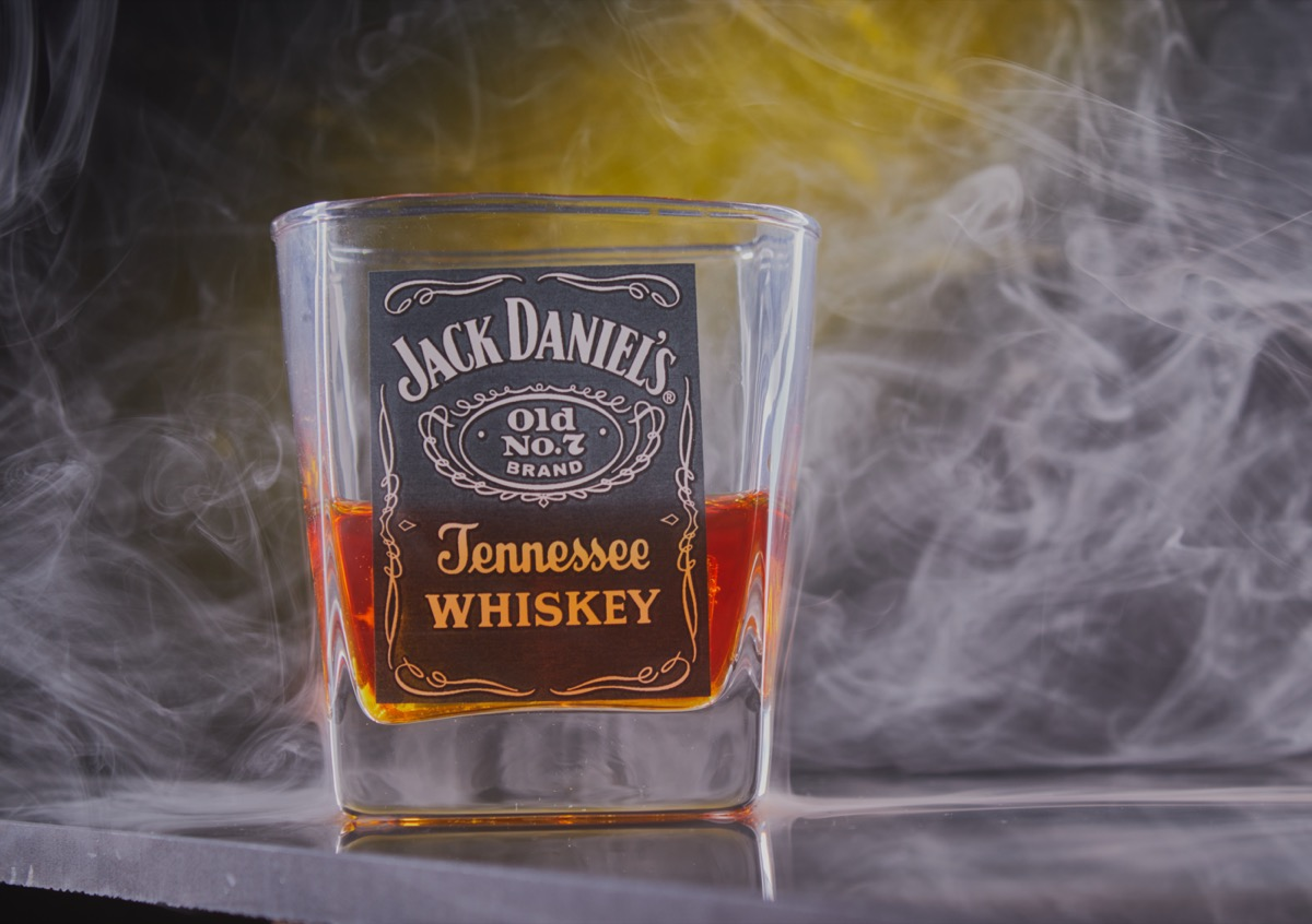 A shot glass of Jack Daniel's in a smoky background