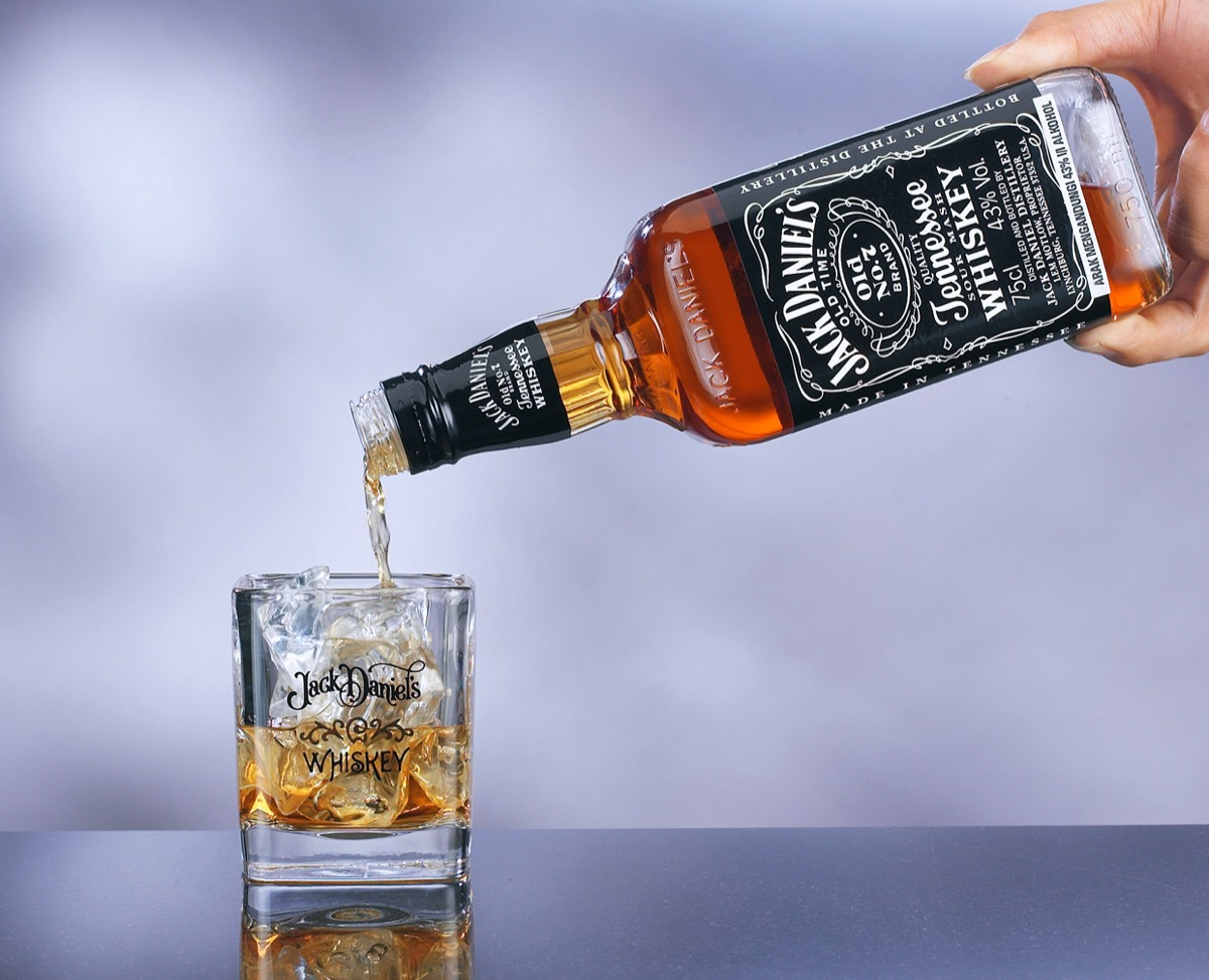 A hand pouring Jack Daniel's in a glass