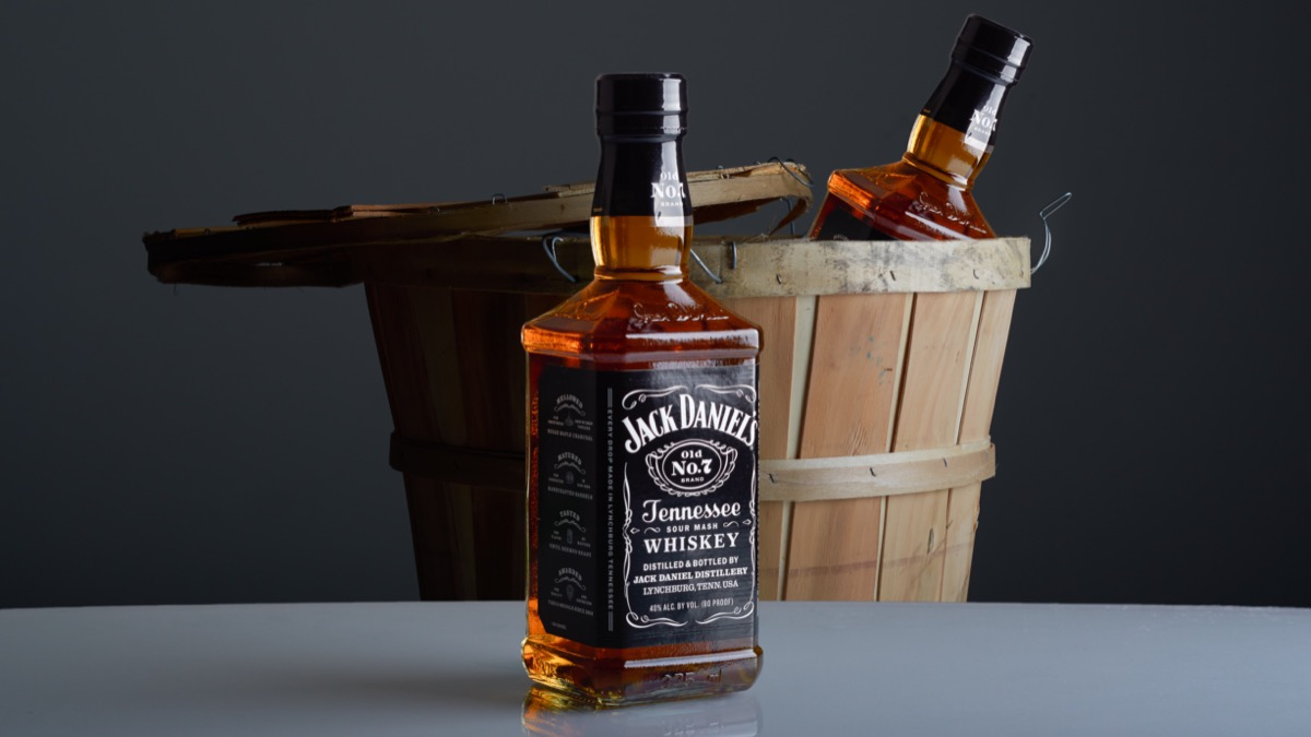 Bottles of Jack Daniel's on table and in a barrel