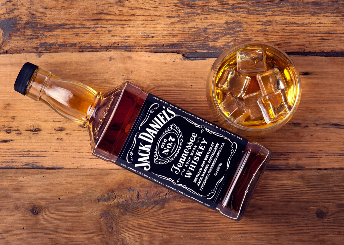 Jack Daniel's in a glass and bottle on a wooden table