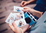 Close up of woman's hands holding instant photos taken on polaroid camera on summer vacations