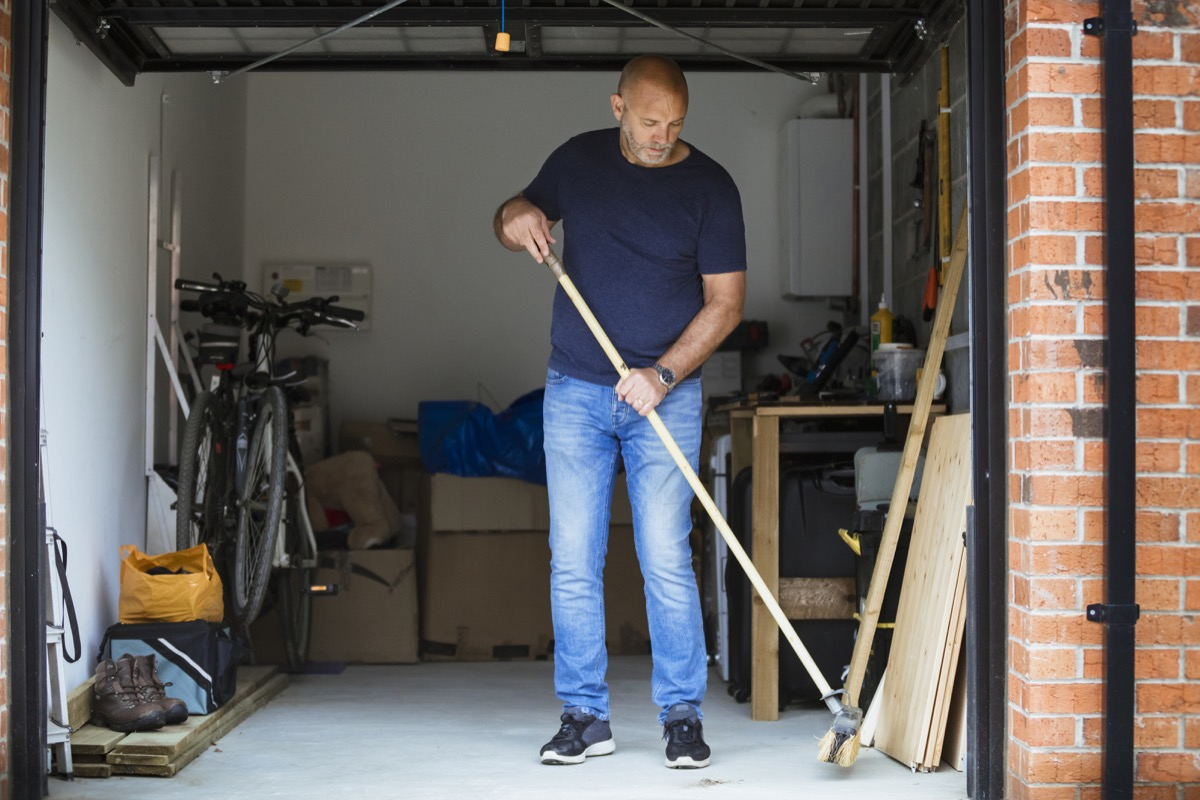 A man is sweeping the floor up his home garage with a large brush. The garage door is open.
