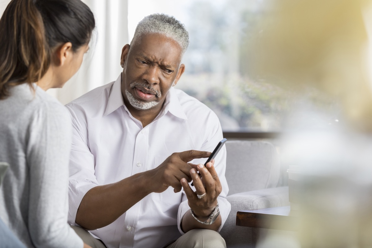 Confused senior man shows something on a smartphone to female friend.