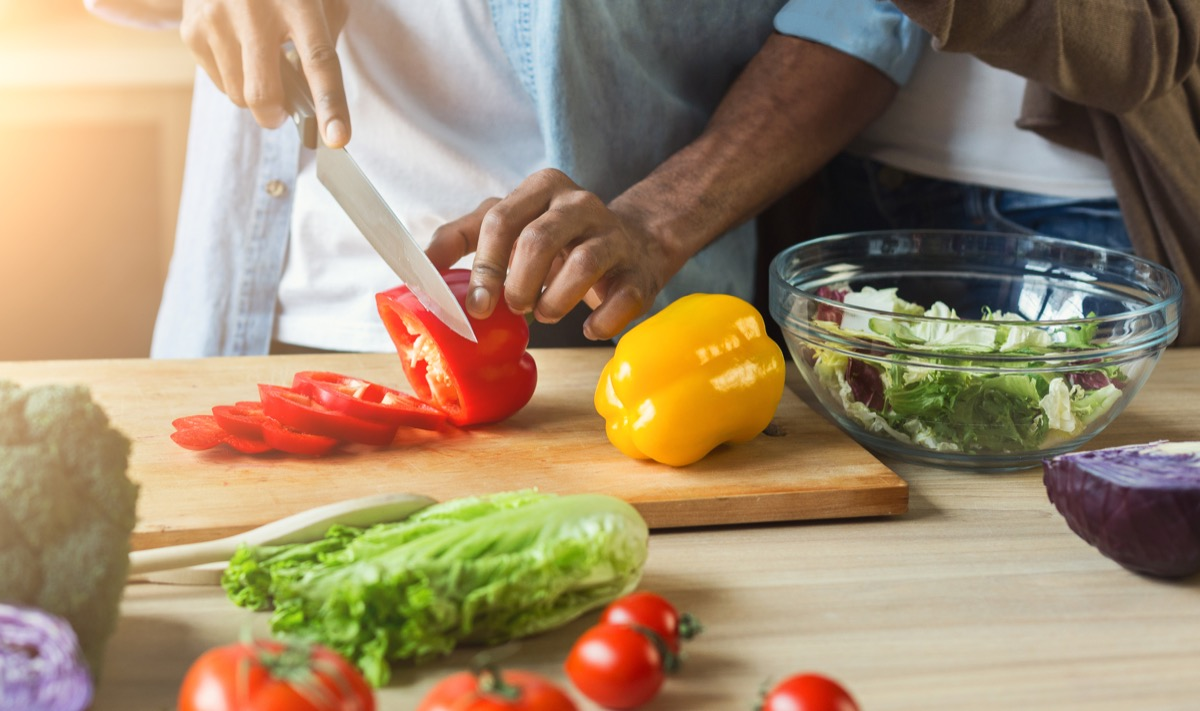 man cutting vegetables for healthy vegetarian salad in kitchen, closeup
