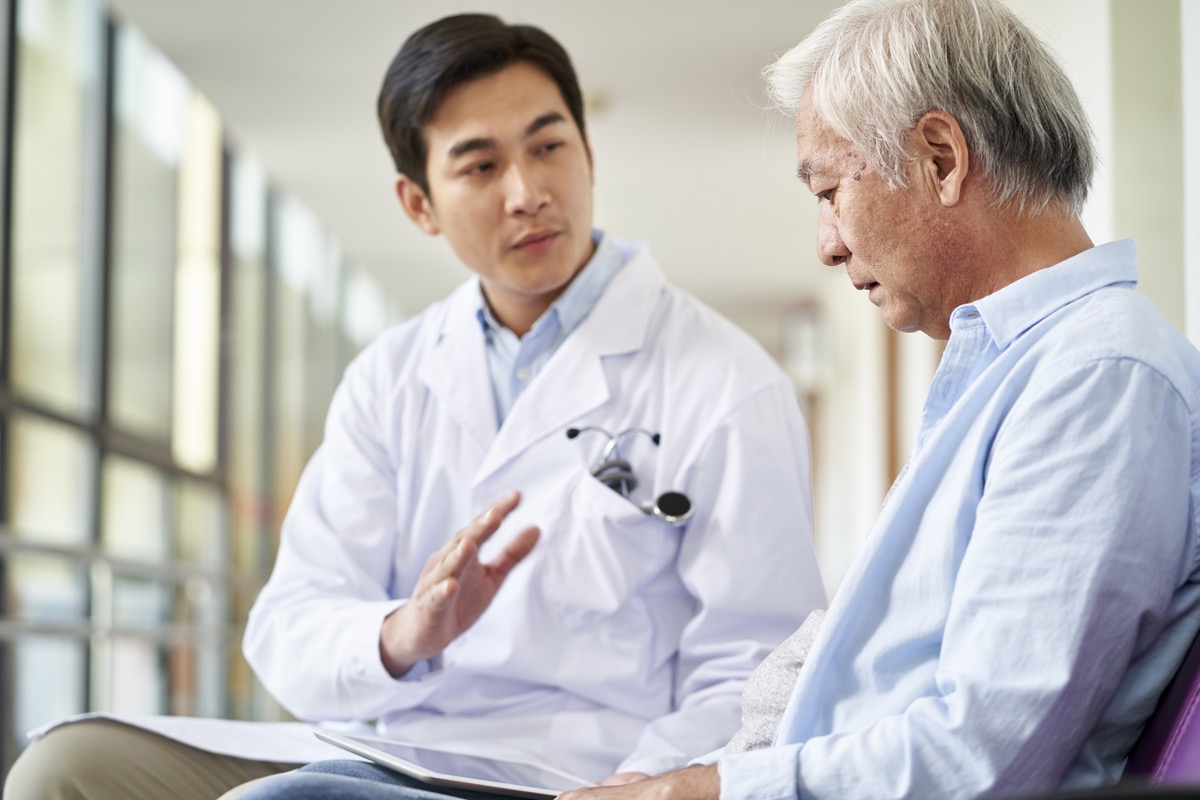 doctor talking and explaining test result and diagnosis to demoralized elderly patient in hospital hallway