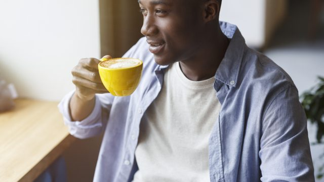 A young man drinking a cup of coffee