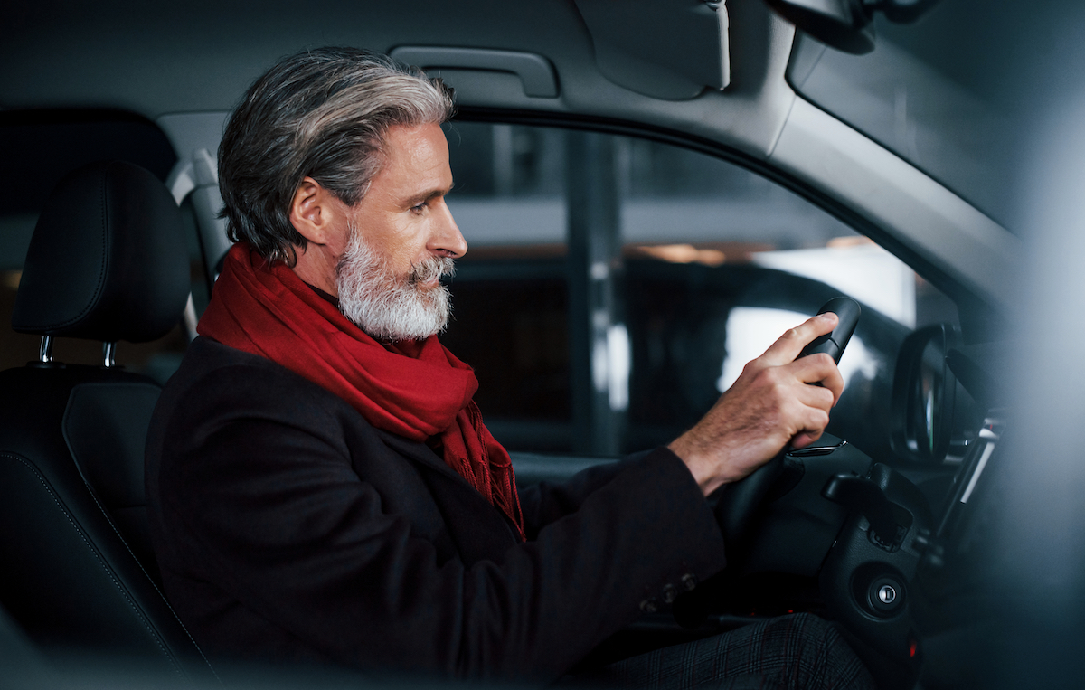 Side view of senior man with grey hair in a car.