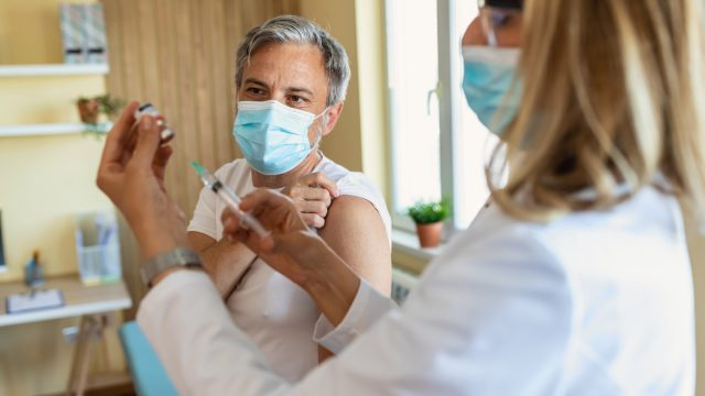A man wearing a face mask about to get a COVID-19 vaccine from a healthcare worker
