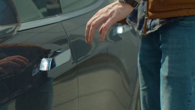 Man opens the door of Tesla Model S.