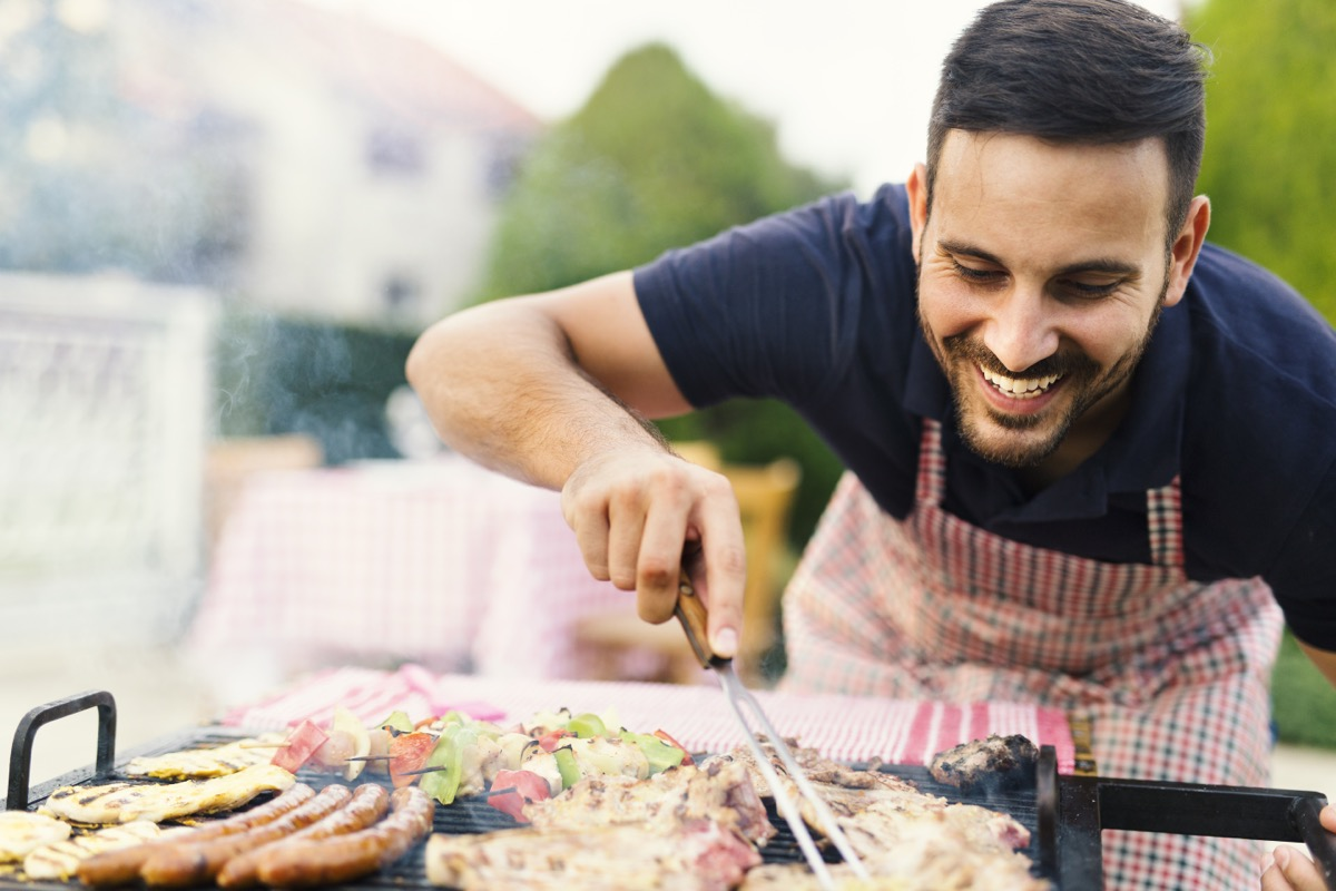 30-something man checking meat on the grill