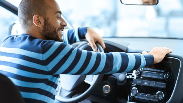 A man wearing a blue sweater sitting inside a car with a happy look on his face