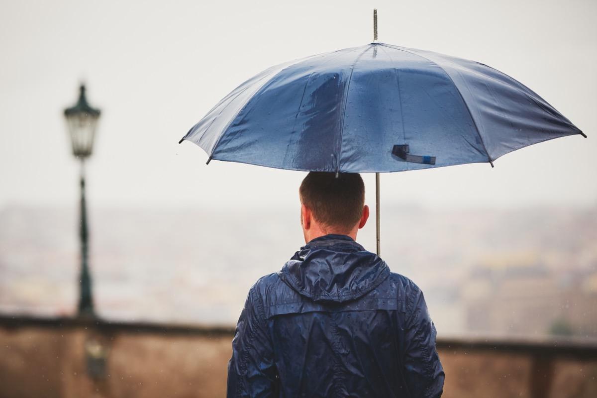 man holding umbrella outside in rain