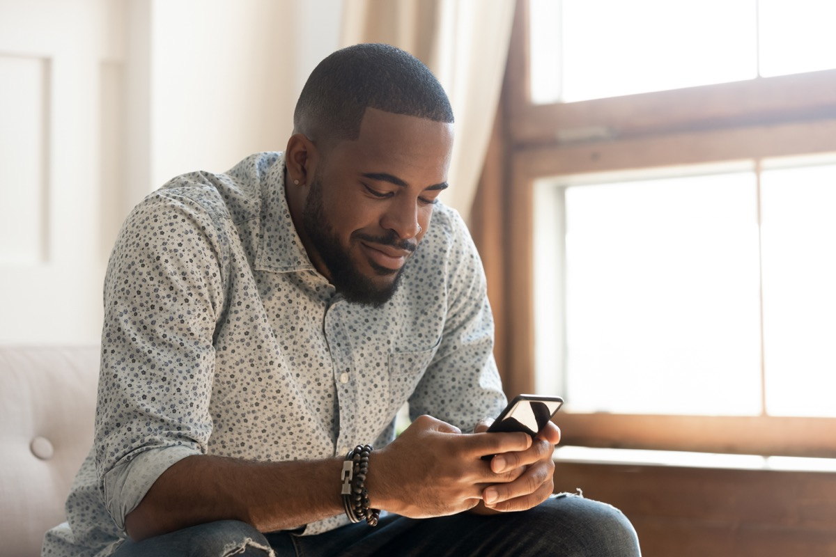 man holding smartphone texting message or play mobile game