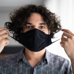 A young man putting on a face mask inside his home