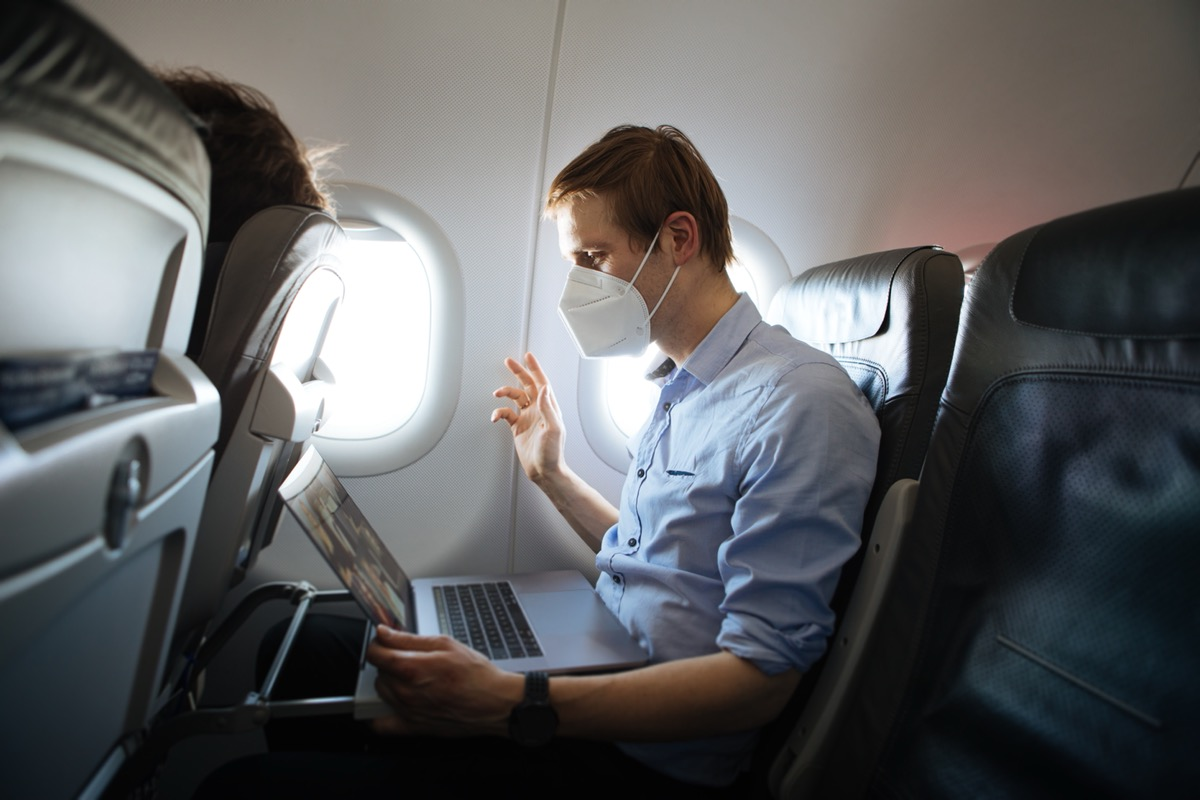 man in his 30s or 40s wearing face mask for COVID protection and waving at laptop in airplane seat