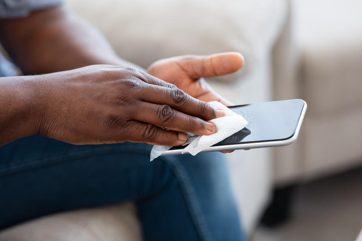 man hands wipe the touch screen phone antibacterial wipes