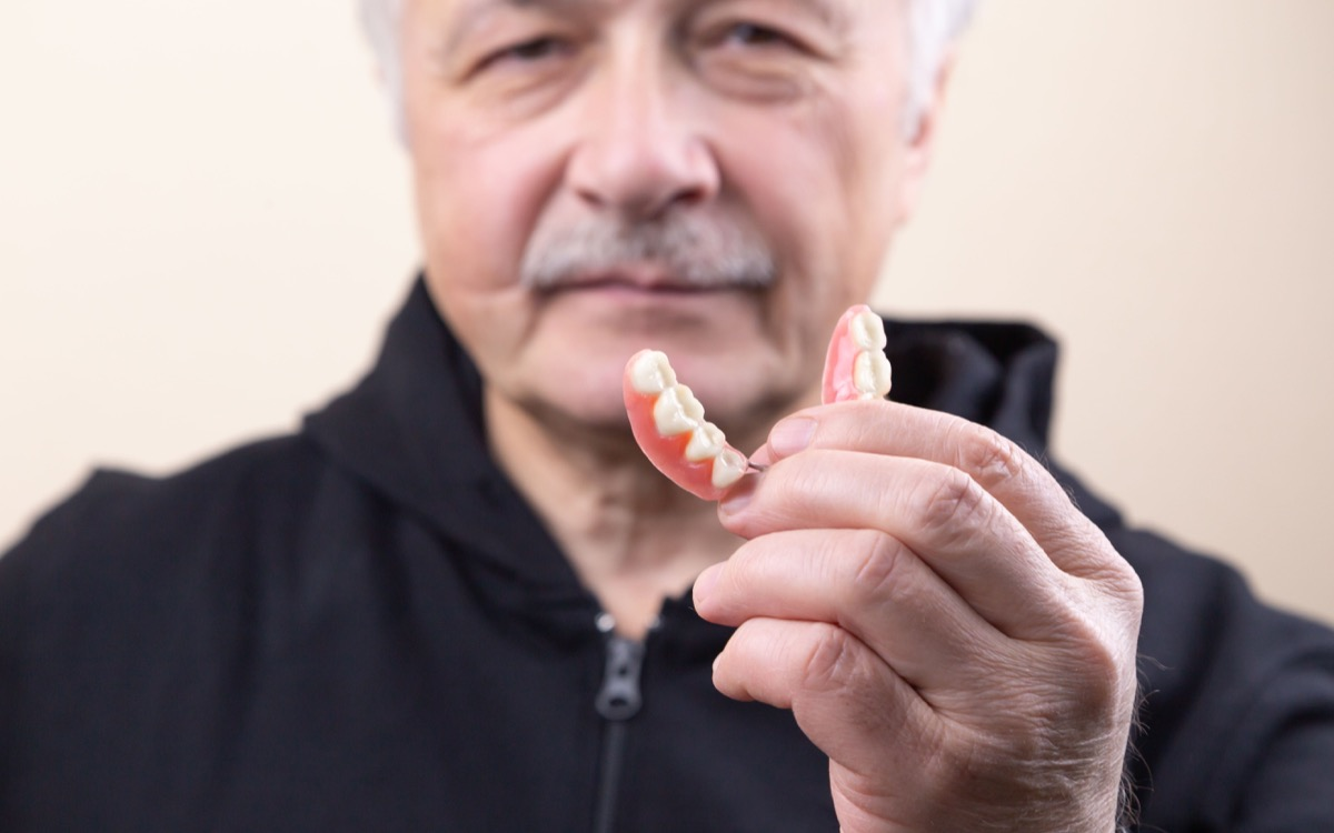 An old gray-haired man holds his denture. The man puts on the denture. Implant. Orthodontics. Old age. Teeth. Jaw. Advertising. The close plan. View from above. Removable denture.