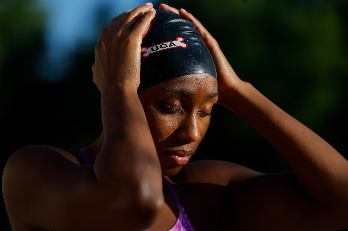 Natalie Hinds puts on her swim cap to train in a residential pool on May 15, 2020 in Athens, Georgia. Due to the COVID-19 pandemic, many elite athletes have been forced to adjust training locations and regimens.