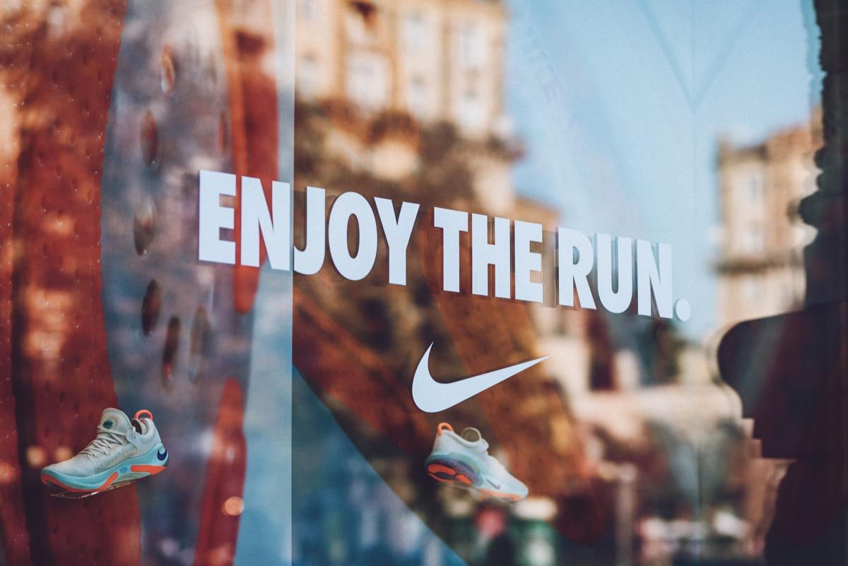 Nike logo brend sign on city street. Signboard of Nike logo on store, shop, mall, boutique. Kiev, Ukraine - September 02, 2019.