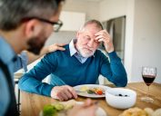 An adult hipster son comforting frustrated senior father indoors at home, eating light lunch.
