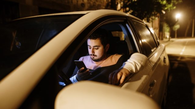 A young man parked with his car looking at his smartphone