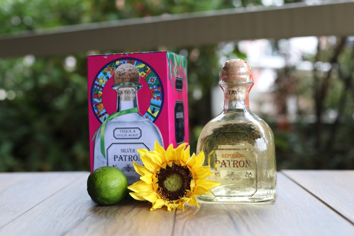 Bottle of Patron next to a flower and lime