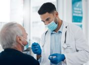 Cropped shot of a handsome young male doctor testing a senior patient for covid