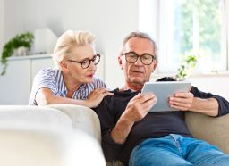 A senior man and woman look at a tablet while sitting on the couch