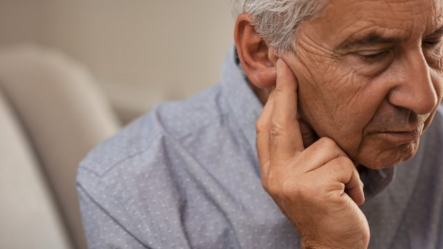 A senior man holding his ear suffering from hearing impairment or loss