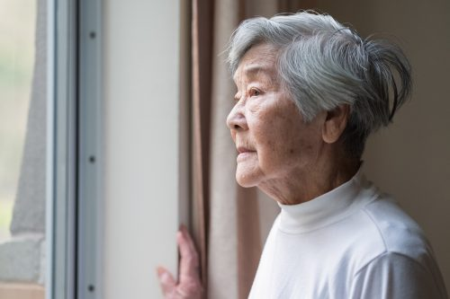A senior woman looking out the window of her home