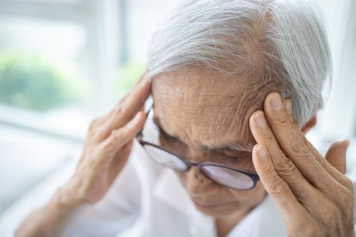 A senior woman rubbing her head with potential signs of a stroke