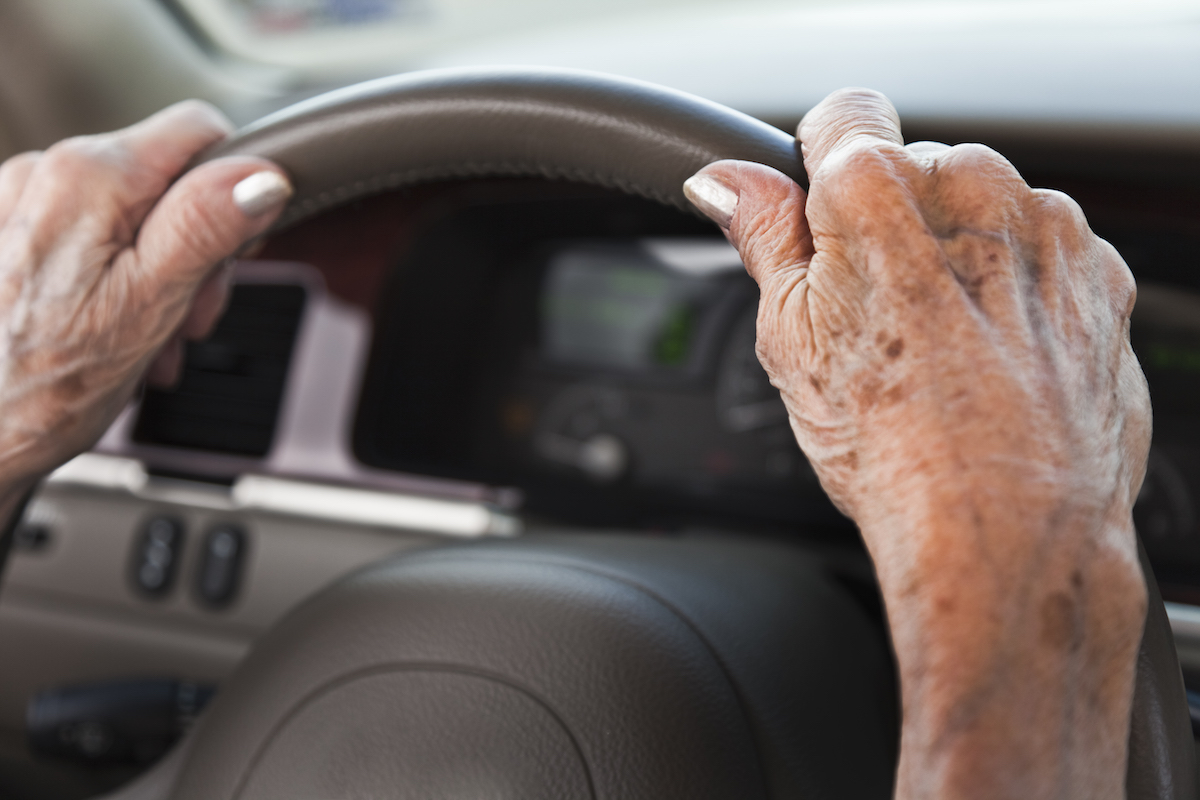 Senior woman driving car with hands on steering wheel.